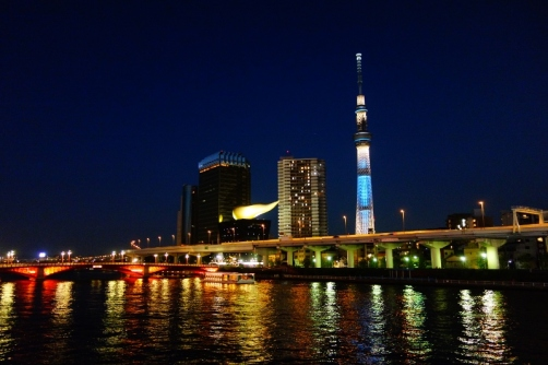 Tokyo Skytree and the Asahi Beer Hall all lit up at night next to the Sumida River (Tokyo, Japan)